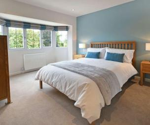 photo of neutral beige blue brown white bedroom with feature wall