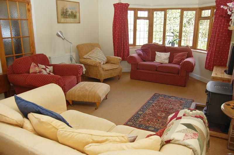 photo of comfy beige brown red living room lounge with wood burner