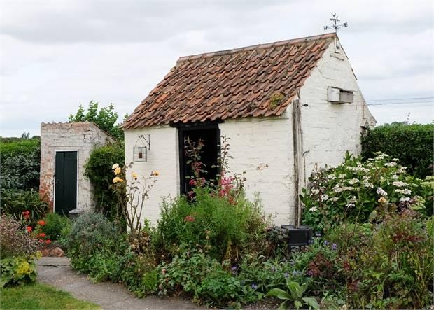 Brick outbuilding (former wash house) with replaced pan tiled roof