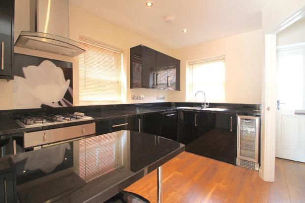 Kitchen has high gloss cabinets