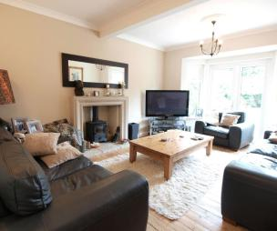 photo of beige black white living room lounge with bare floorboards wood burner and coffee table