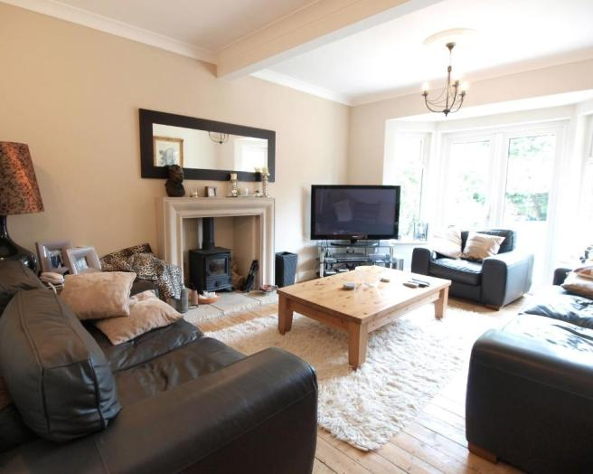 photo of beige black white living room lounge with bare floorboards fireplace wood burner and coffee table