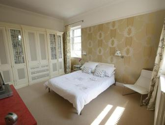 photo of beige brown white bedroom with feature wall