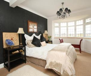 photo of beige black white bedroom with window black lights black wallpaper carpet furry rug rugs soft furnishings and bed furniture