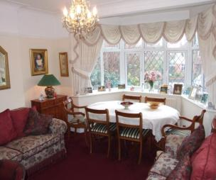 photo of cosy ruched dining room lounge/dining room with chandelier bay window leaded windows pelmet