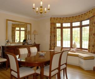 photo of classic beige brown dining room with bay window and bench seat dining table & chairs