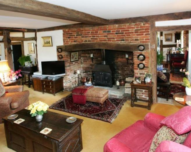 photo of comfy rustic beige brown lounge with fireplace inglenook fireplace open fireplace and treasure chest