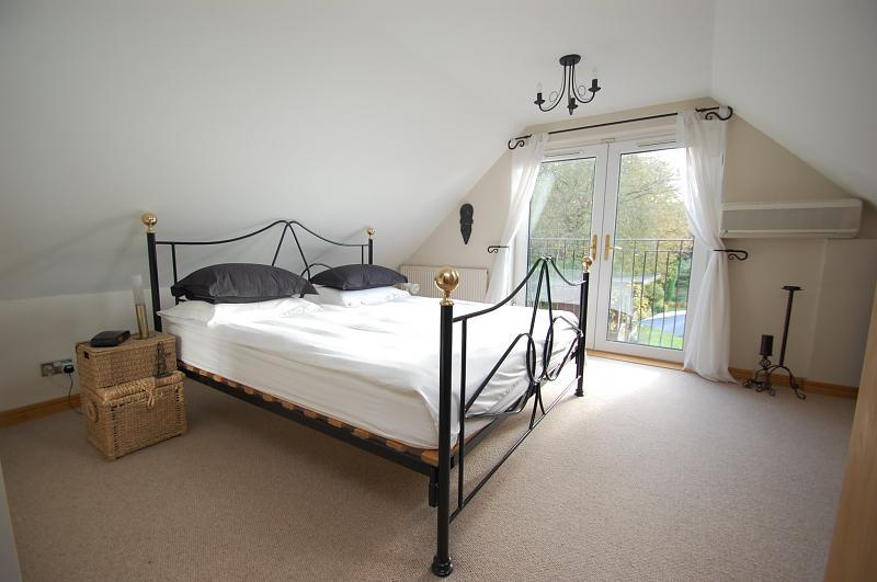 photo of brown white wicker bedroom with carpet and metal bedstead