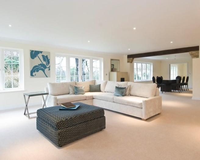 photo of open plan beige white living room lounge with artwork and furniture ottoman