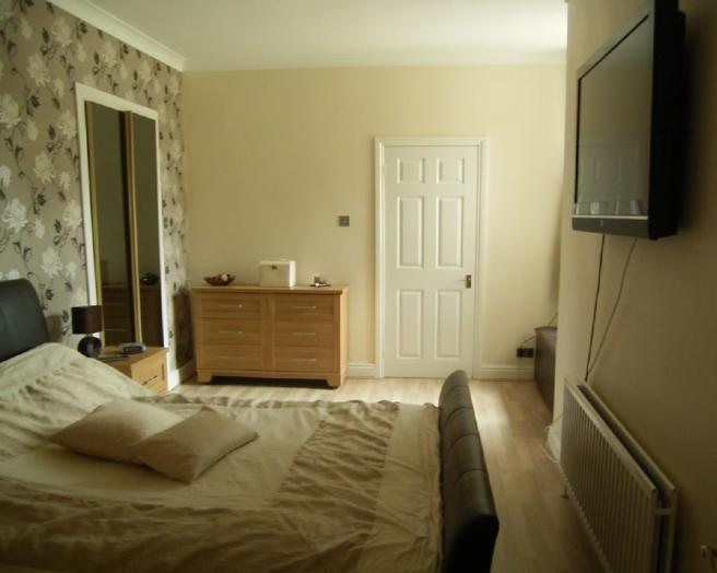 photo of beige brown cream olive bedroom with flooring laminate flooring feature wall wallpaper