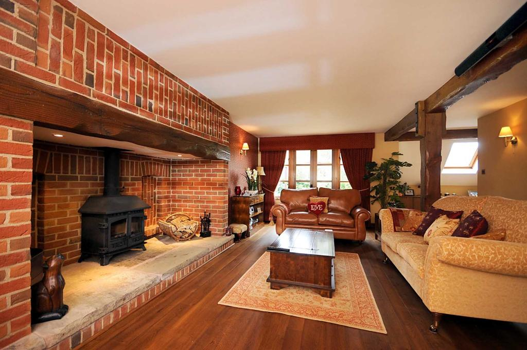 photo of traditional beige brown orange lounge with hardwood floor inglenook fireplace