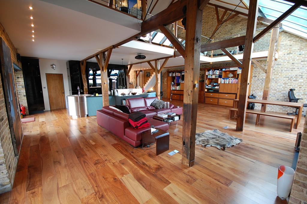 photo of contemporary open plan purple living room lounge mezzanine with exposed beams hardwood flooring