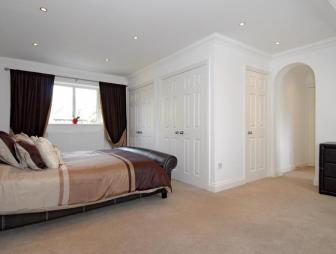 photo of neutral beige white bedroom with fitted wardrobes spotlights carpet