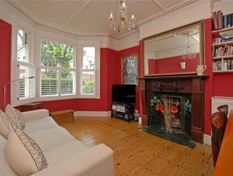 photo of beige orange red living room lounge with chandelier bay window fireplace varnished floorboards
