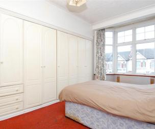 photo of beige white bedroom with carpet carpeted and fitted wardrobe furniture