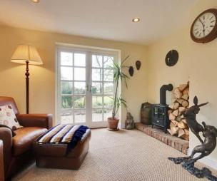 photo of textured beige brown kitchen living room with fireplace log burner and colours wood burner carpet sculpture wall clock and leather chair