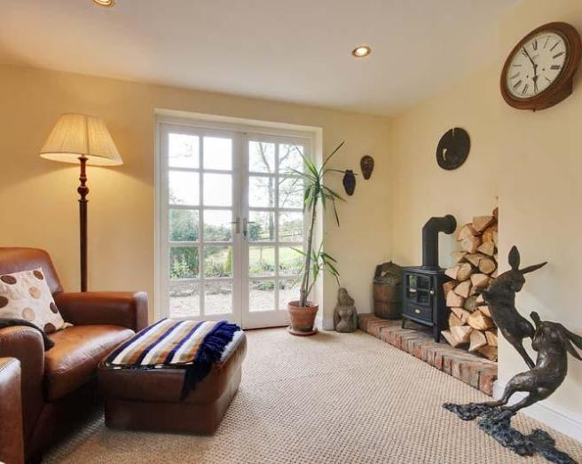 photo of textured beige brown kitchen living room with log burner and colours wood burner carpet sculpture wall clock and leather chair