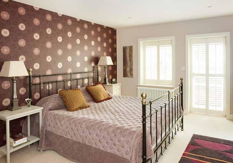 photo of brown bedroom with feature wall wallpaper and bed bedknobs furniture metal bedstead