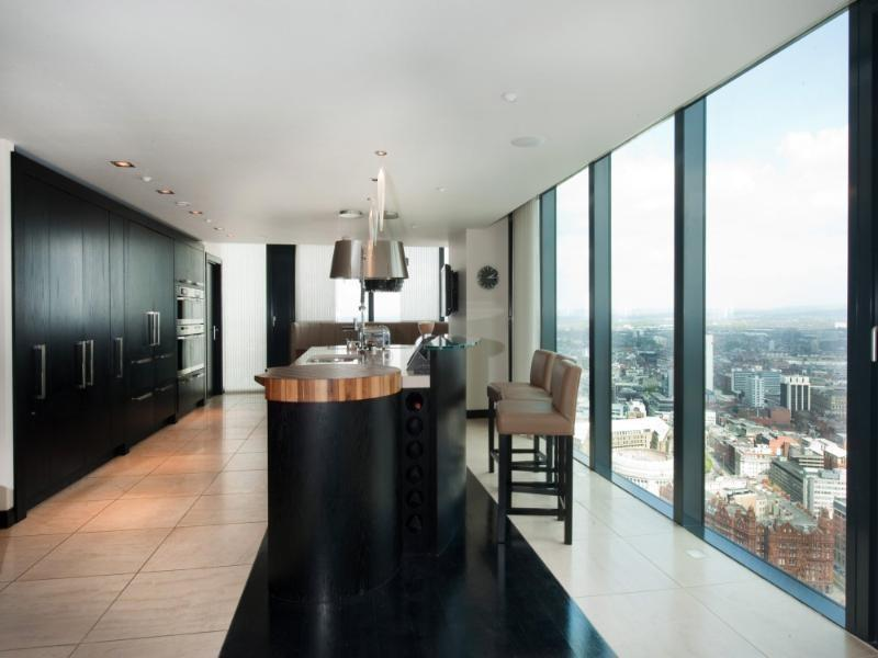 photo of contemporary luxury open plan black blue white dining room kitchen penthouse with picture window and bar stools wine rack view views