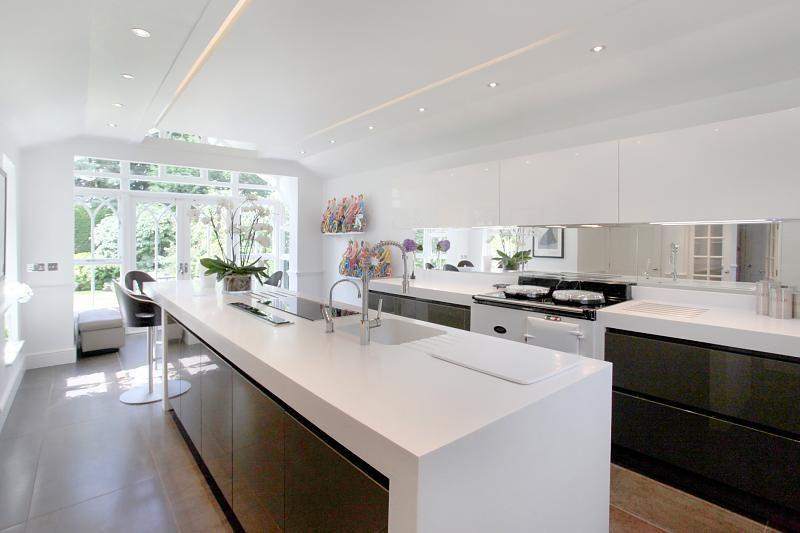 photo of luxury open plan white kitchen with massive kitchen island