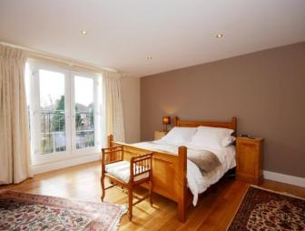 photo of modernish simple beige brown mocha white wooden bedroom with big windows wooden floors feature wall rugs