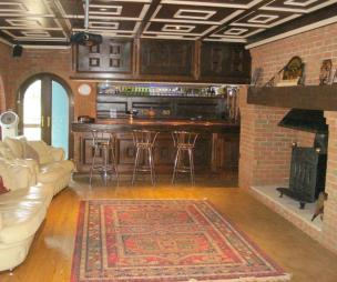 photo of beige brown white leather lounge with bar brick fireplace fireplace wood burner