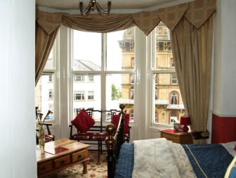 photo of classic beige brown white bedroom with bay window sash window pelmet