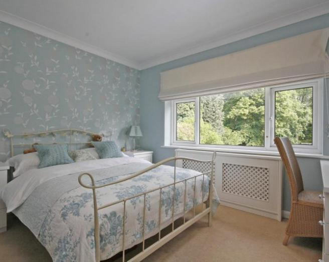 of pretty blue white bedroom with covered radiator blinds roman blind