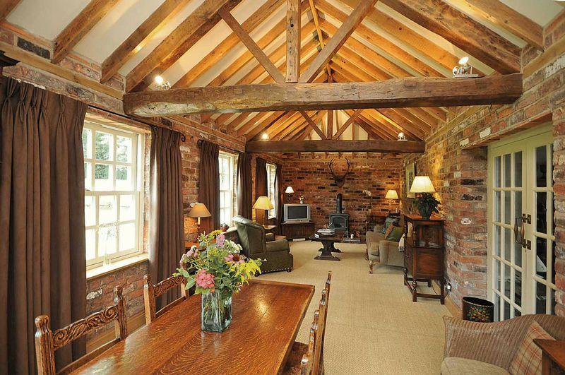 photo of rustic brown exposed bricks jute barn living room with exposed beams wood beams wood burner and cottage