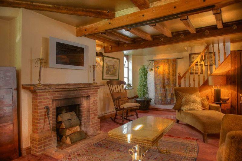 photo of beige brown orange living room lounge sitting room with brick fireplace exposed beams