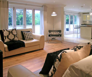 photo of contemporary modern open plan beige white kitchen living room lounge with cushions soft furnishings