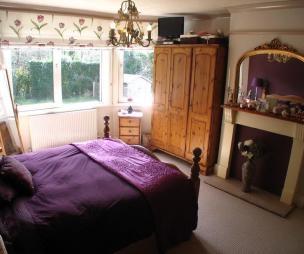 photo of black brown purple bedroom main bedroom with chandelier carpet roller blind