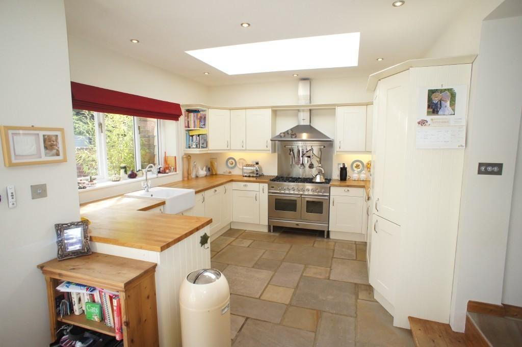 photo of modern beige maroon red white flagstone floor stone kitchen with wooden worktop worktop skylight blinds roman blind