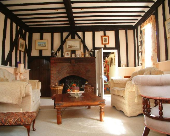 photo of beige brown lounge with beams brick fireplace fireplace