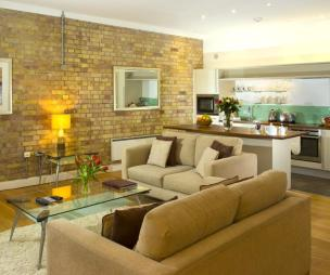 photo of open plan beige brown orange brick wall exposed brick frosted glass living room with lighting and glass coffee table