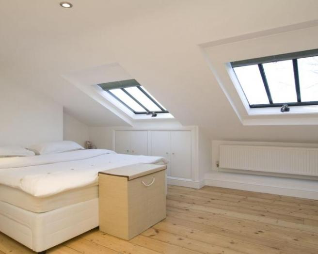 photo of beige white bedroom loft conversion with gabled ceiling skylight