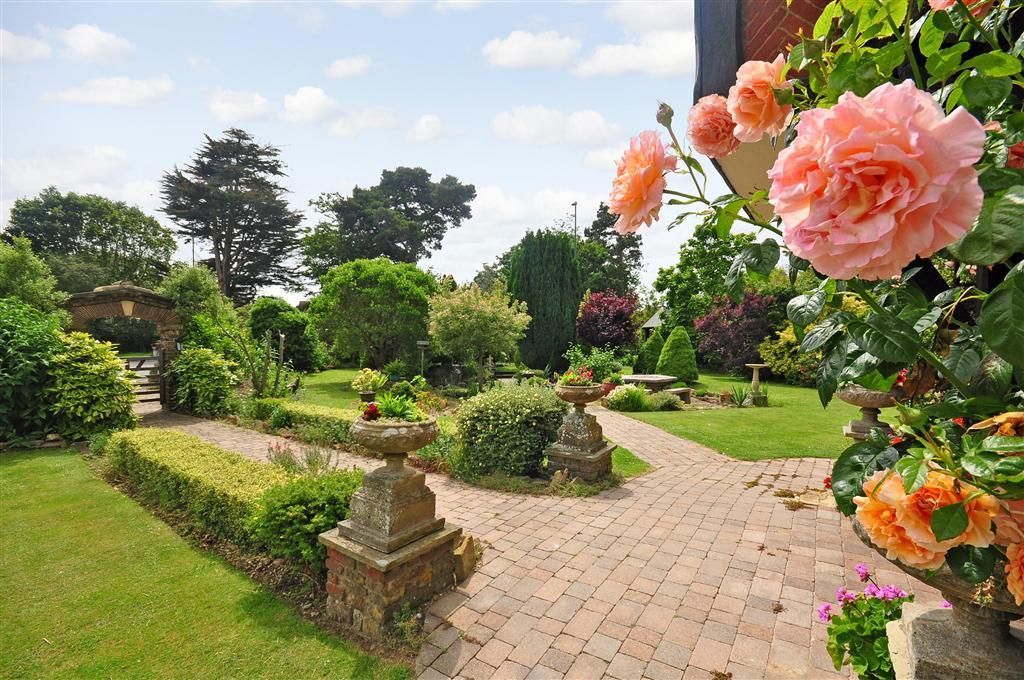 photo of brick paving garden with archway flowers and front garden sunny