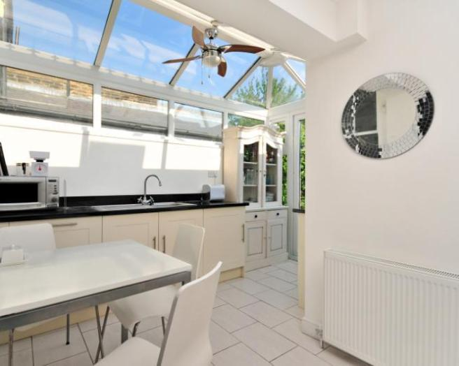 photo of airy bright beige white kitchen kitchen extension with skylight