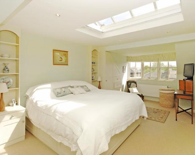 photo of beige white white with a hint of apple bedroom with skylight