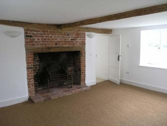 photo of brown white brick jute with beams inglenook fireplace