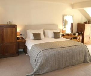 photo of spacious beige brown creamy grey wood bedroom with mirror mirrors carpet and bed double bed furniture
