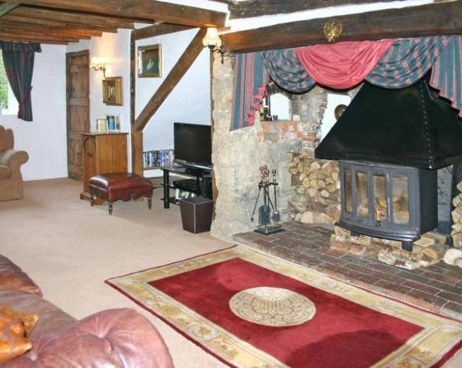 photo of cosy beige pink red white lounge with inglenook fireplace