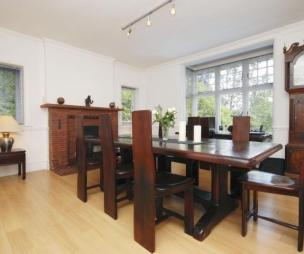 photo of beige white dining room with brick fireplace wooden floor grandfather clock and artistic chairs