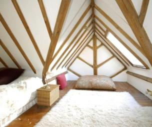 photo of white loft conversion with exposed beams furry rug rugs soft furnishings