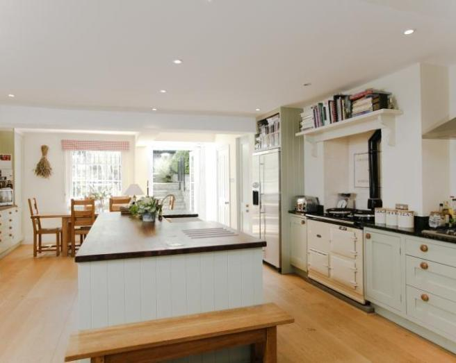 photo of large cream pastel white kitchen with kitchen island and aga