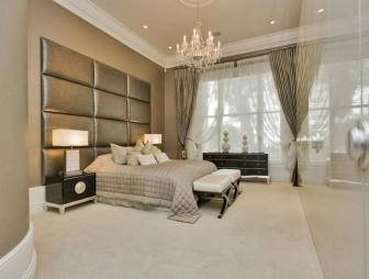 photo of contemporary modern beige gold bedroom with chandelier fitted wardrobes carpet and headboard