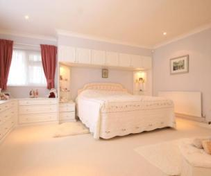 photo of beige pink bedroom with fitted drawers spotlights carpet and fitted bed surround furniture