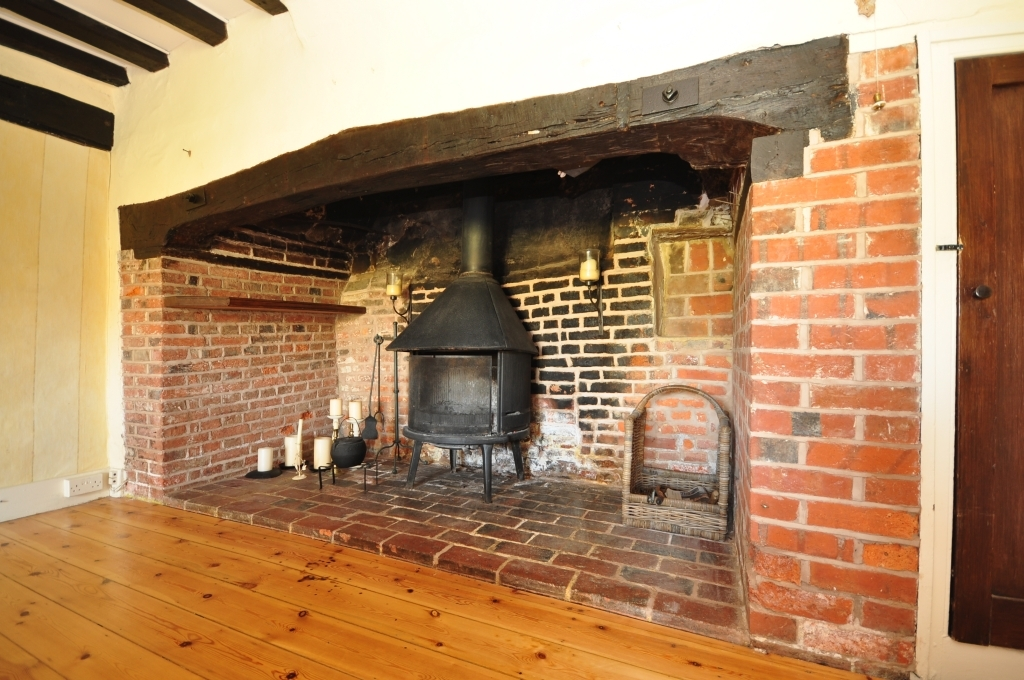 photo of beige brown orange with inglenook fireplace varnished floorboards wood burner