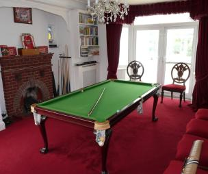 photo of brown red white dining room with brick fireplace fireplace and furniture pool table
