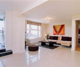 photo of open plan beige pink white marble living room with artwork and pouffe